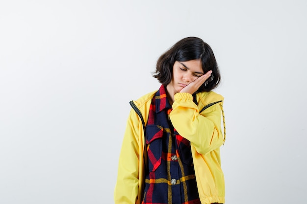 체크 셔츠, 재킷에 그녀의 손에 얼굴을 베개하고 졸린 전면보기를 찾고 어린 소녀의 초상화