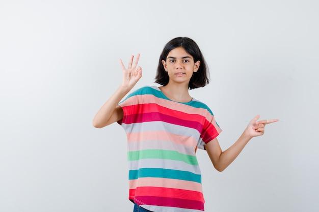 脇を向いて、tシャツにokサインを表示し、誇らしげな正面図を探している少女の肖像画