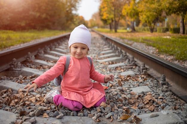숲 속의 기차 트랙에 앉아 있는 어린 소녀의 초상화
