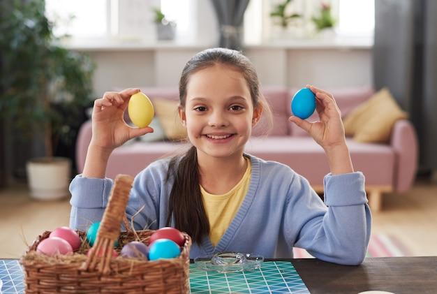 테이블에 앉아 부활절 달걀을 그리는 동안 카메라를 보며 웃고 있는 어린 소녀의 초상화