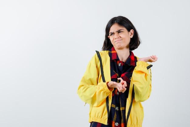 チェックのシャツ、ジャケットで手のひらを広げて不満を持っている正面図を探している少女の肖像画
