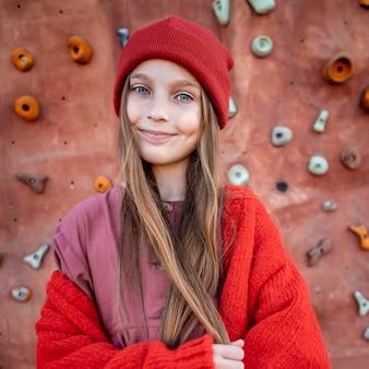 Портрет маленькой девочки, стоящей рядом со скалодромом