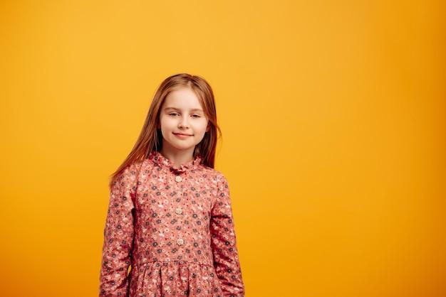 Портрет маленькой девочки в красивом платье, изолированном на желтом фоне