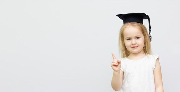 흰색 배경에 고립 된 복사본 공간 대학원 모자를 쓰고 어린 소녀의 초상화