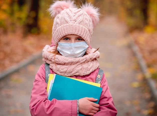 방과 후 가을 공원을 산책하는 동안 보호 얼굴 마스크를 착용하는 어린 소녀의 초상화