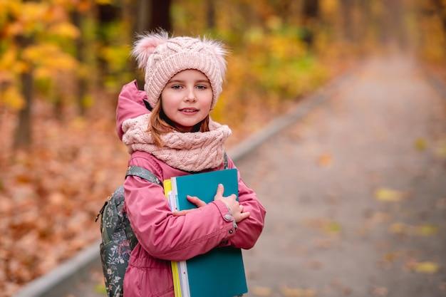 가을 공원 도로에 서있는 동안 배낭 들고 폴더와 어린 소녀의 초상화