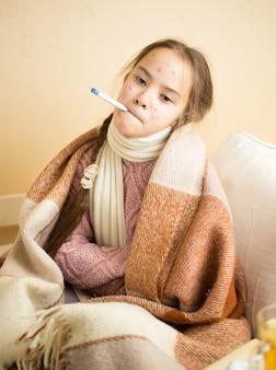 Портрет маленькой девочки с ветряной оспой, держащей во рту термометр