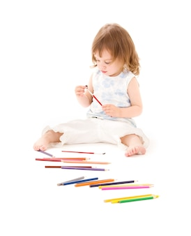 白い壁の上の色鉛筆を持つ少女の肖像画