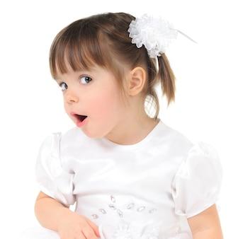 明るい背景に面白い表情を持つ少女の肖像画。白い服とヘアアクセサリーの子供