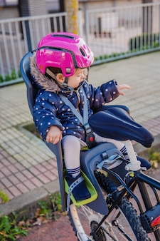 산책을 할 준비가 된 자전거 좌석에 앉아 머리에 보안 헬멧을 쓴 어린 소녀의 초상화. 안전하고 아동 보호 개념입니다.