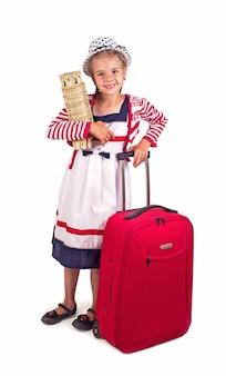 Портрет маленькой девочки с дорожным чемоданом и шляпой, держащей игрушечную бумажную пизанскую башню, изолированную на белом