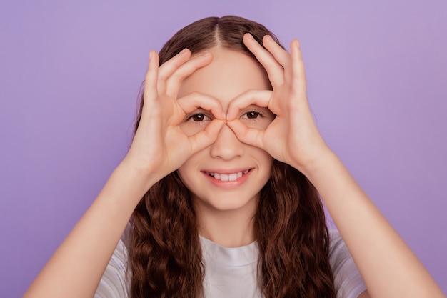 小さな子供の女の子の肖像画は、紫色の背景の上に分離された大丈夫サイン目を作ります