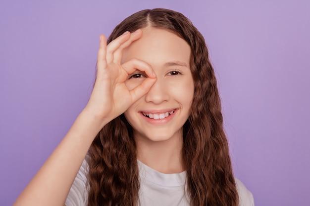 小さな子供の女の子の肖像画は、紫の背景の上に分離された片手で大丈夫サイン目のスペックを作成します