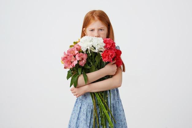 Портрет маленькой обиженной рыжеволосой девушки с веснушками, недовольная выглядит благоговейно, держит букет и закрывает лицо им, носит синее платье, на белом фоне.