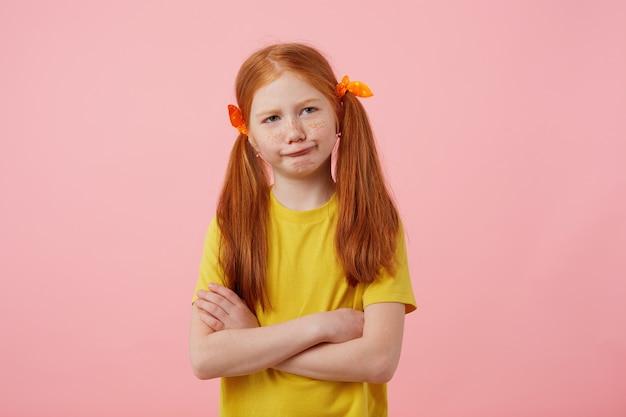 Портрет маленькой задумчивой рыжеволосой девушки с веснушками с двумя хвостами, недовольная выглядит благоговейной, носит желтую футболку, стоит со скрещенными руками на розовом фоне.