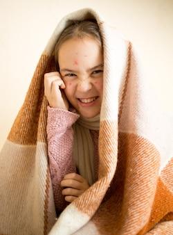 Портрет маленькой царапающей девочки с ветряной оспой, сидящей на кровати