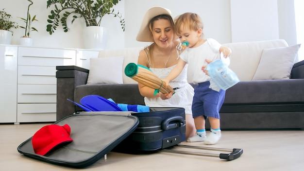 休日の旅行のためにスーツケースに物を詰める母親を助ける小さな幼児の少年の肖像画。
