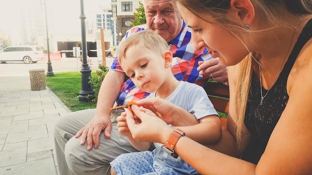 Портрет маленького мальчика с молодой матерью и отцом, сидящим на скамейке в парке и играющим с маленьким пластиковым игрушечным вертолетом