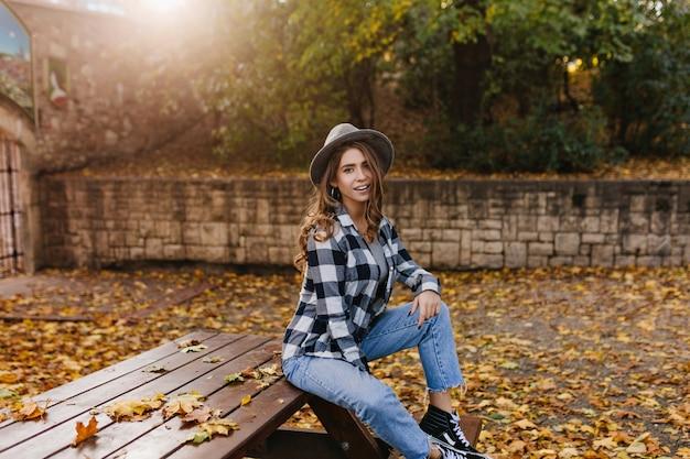 Портрет одинокой девушки с грустной улыбкой, сидящей в парке в окружении золотых листьев