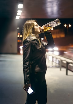 고속도로에서 병에서 술을 마시는 외로운 여자의 초상화