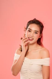 Портрет длинные волосы азиатских молодая красивая женщина улыбаться и касаться ее лицо, изолированных на розовый. счастливая женщина улыбается в студии.