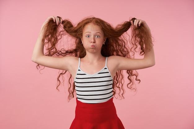 분홍색 배경 위에 서있는 동안 그녀의 빨간 머리를 가지고 노는 장발 곱슬 소녀의 초상화, 뺨을 부풀리고 재미를 만들고, 제기 눈썹으로 카메라를 찾고