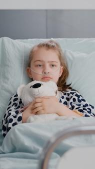 Портрет одинокого больного маленького ребенка, отдыхающего в постели, держа в руках мишку, смотрящую в камеру во время выздоровления в больничной палате. госпитализированный ребенок ждет лечения