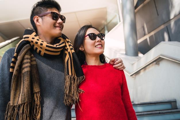 ショッピングを楽しんで、モールで一緒に楽しんでいる素敵なアジアのカップルの肖像画。愛とショップのコンセプト。