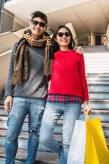 カラフルな買い物袋を持って買い物を楽しんで、モールで一緒に楽しんでいる素敵なアジアのカップルの肖像画。
