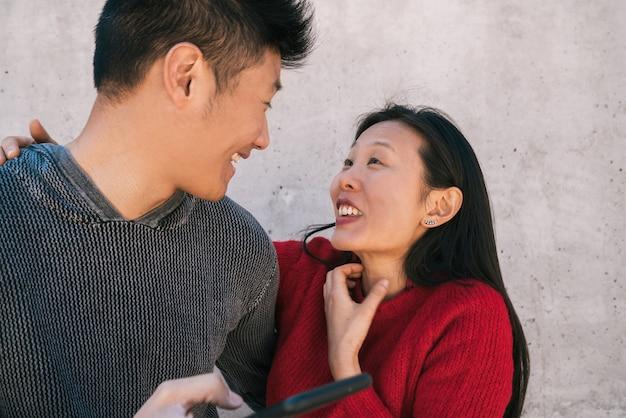 一緒に楽しい時間を過ごしながら携帯電話を見ている素敵なアジアのカップルの肖像画。愛とテクノロジーのコンセプト。