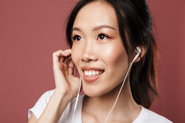 기본적인 옷을 입은 사랑스러운 아시아 여성의 초상화는 웃고 있고 빨간 벽에 격리된 이어폰으로 음악을 들으며