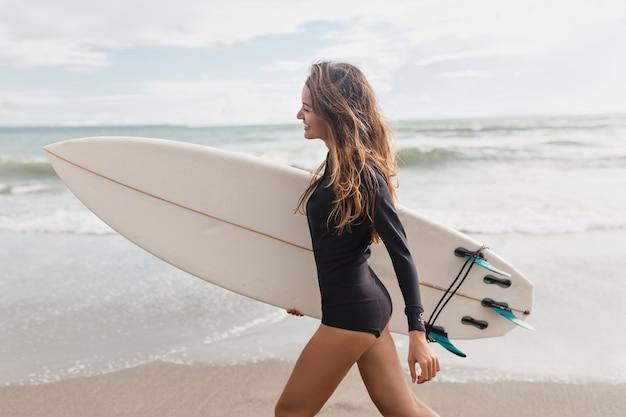 彼女のレッスンのために海岸に沿ってサーフボードに行くサーフィンのための衣装に身を包んだ長い髪を持つ素敵な魅力的な若い女性の肖像画。アクティブなライフスタイル、スポーツ、夏、熱帯のビーチ