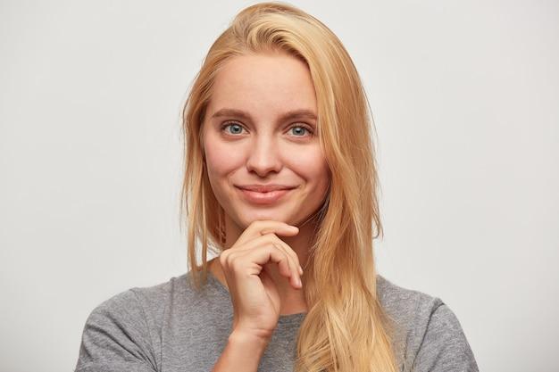 Портрет прекрасной красивой уверенной блондинки с голубыми глазами, выглядит счастливой