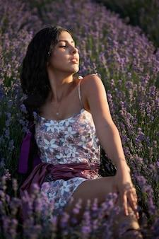 라벤더 밭에서 사랑스러운 갈색 머리 여자의 초상화입니다. 카메라 앞에서 포즈를 취하는 여름 라벤더 모델.
