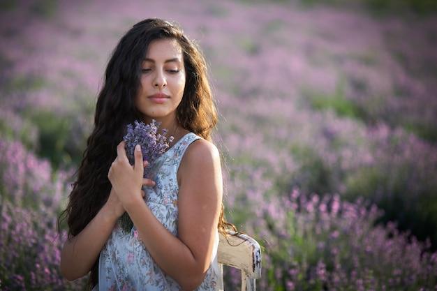 Портрет симпатичной девушки брюнет на предпосылке поля лаванды.