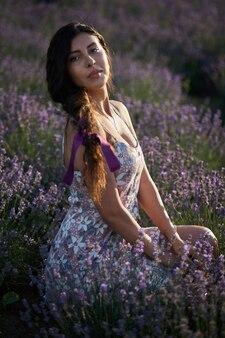 라벤더 밭 배경에 사랑스러운 갈색 머리 소녀의 초상화.