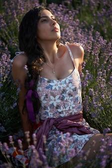 라벤더 밭 장면에 사랑스러운 갈색 머리 여자의 초상화.