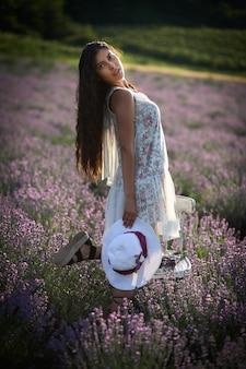 ラベンダーフィールドの背景に帽子をかぶった素敵なブルネットの少女の肖像画。