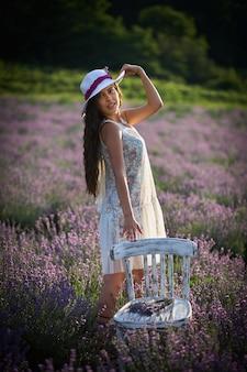 라벤더 밭 배경에 모자를 쓴 사랑스러운 갈색 머리 소녀의 초상화.