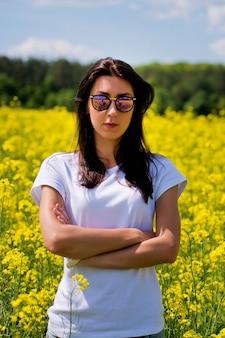サングラスをかけた素敵なブルネットの肖像画は、菜種畑に座っています。 Premium写真