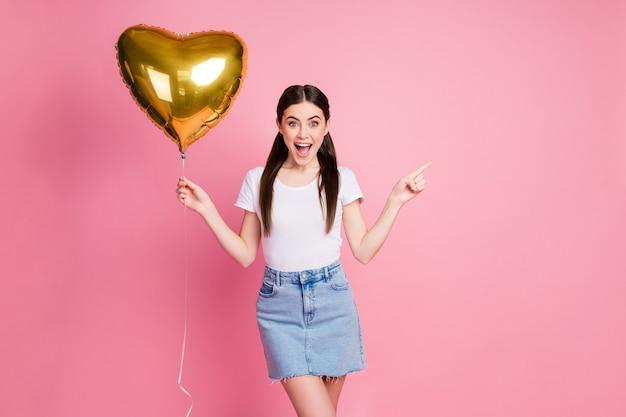 Портрет прекрасной очаровательной девушки, держащей в руке гелиевый шар, показывает пространство для копирования