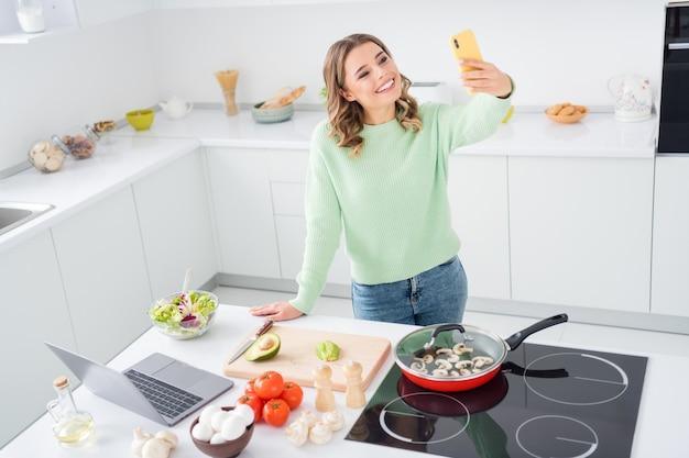 Портрет прекрасной веселой девушки, готовящей вкусное вкусное блюдо, принимая селфи