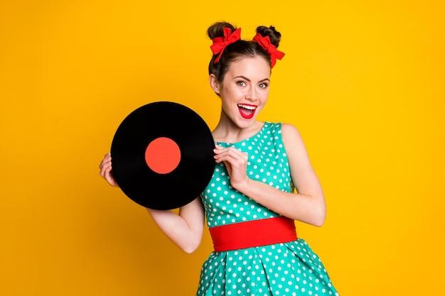 鮮やかな黄色の背景に分離された楽しみを持っているビニールディスクを手に持っている素敵な陽気な女の子の肖像画