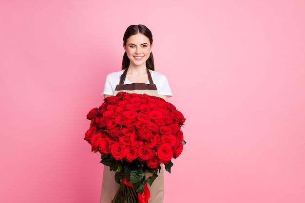 Портрет прекрасной веселой девушки, держащей в руках гигантский роскошный букет красных роз