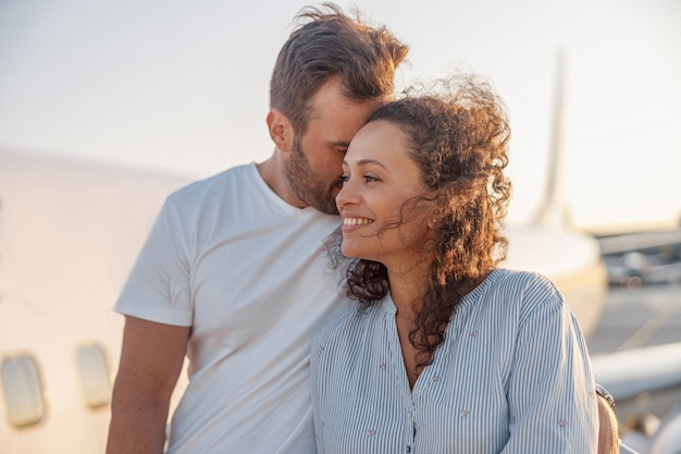 일몰에 비행기에 탑승할 준비가 되어 있는 야외에 서서 행복해 보이는 두 명의 관광객, 남자와 여자의 초상화. 휴가, 라이프 스타일, 여행 개념