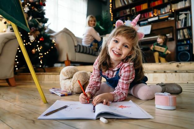 Портрет симпатичного рисунка девушки с красочными карандашами дома. творческая концепция семьи малыш