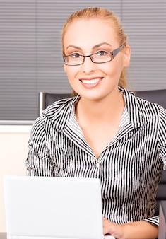 オフィスでコンピューターを持つ素敵な女の子の肖像画