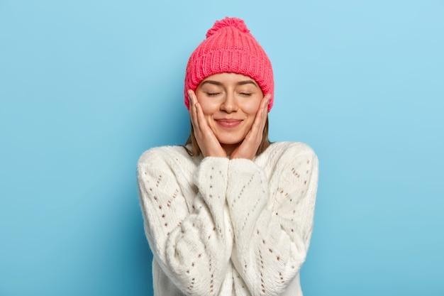 満足のいく表情を持つ素敵な女の子の肖像画は、両方の頬に触れ、目を閉じて、ピンクの帽子と白いセーターを着て、青い壁に対して冬のポーズを楽しんでいます