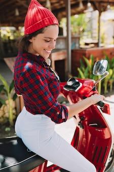 Портрет красивой радостной женщины с темными волосами и милой улыбкой, одетой в яркую рубашку и кепку, белые джинсы, сидящие на велосипеде и улыбки у тропических растений