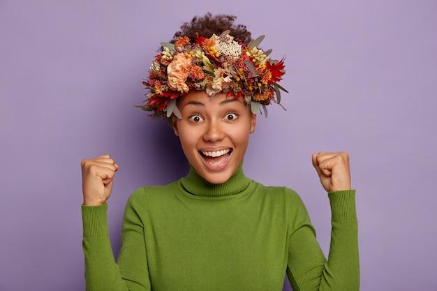 사랑스러운 행복한 여자의 초상화는 주먹을 움켜 쥐고, 운이 좋으며, 열정적 인 표정을 가지고 있으며, 가을 계절 화환을 착용하고, 보라색 배경에 포즈를 취합니다.